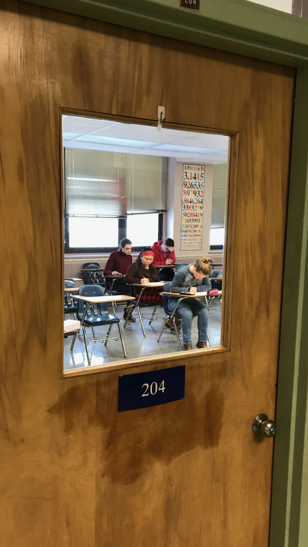 Students taking exams in a classroom.