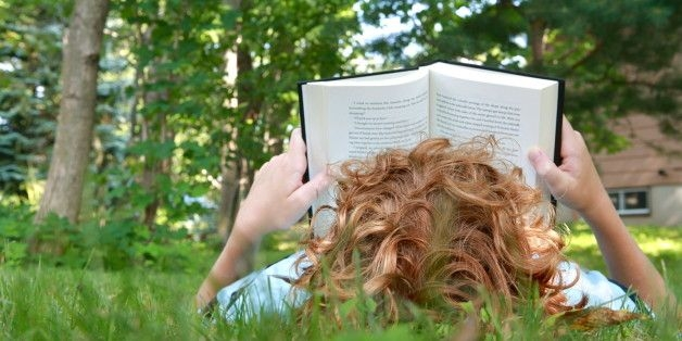 Child lying in grass reading book