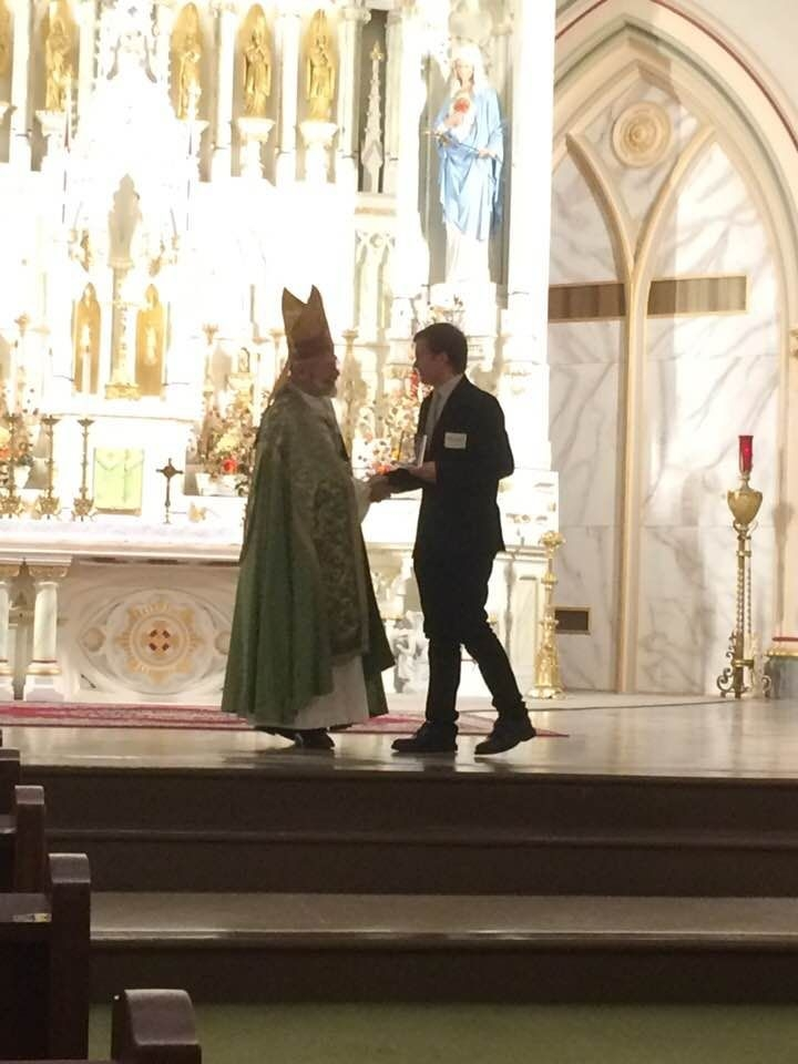 Young man shakes hand with bishop.