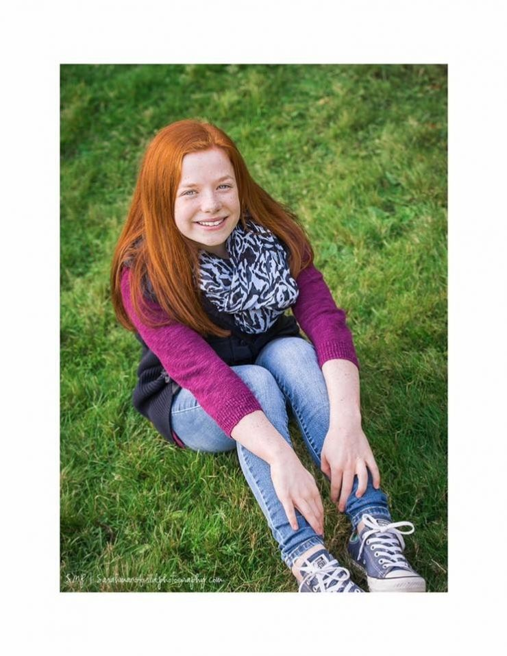 Red haired girl sitting on grass