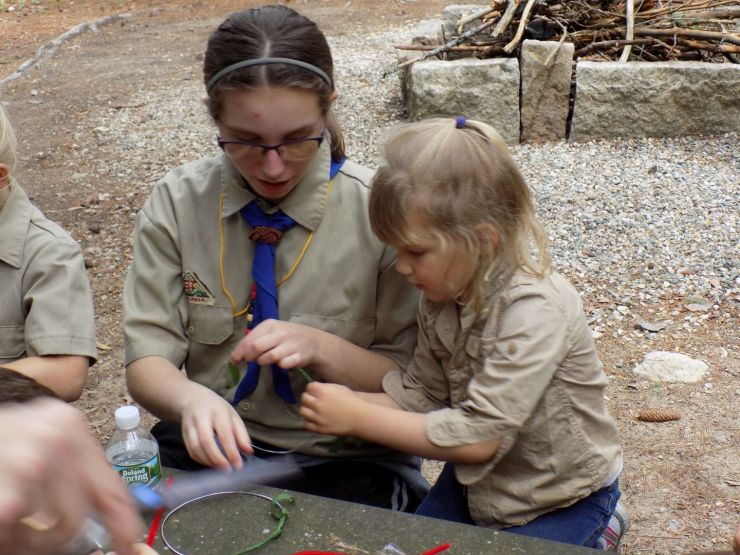 Older Girl Scout helping a younger scout.
